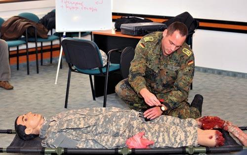 Pierre Prokop, a német hadsereg zászlósa a kanadai CAE (Canadian Aviation Electronics) cég Caesar szimulációs babáján mutatja be az elsősegélynyújtást a NATO Katona-egészségügyi Kiválósági Központ (KEKK) próbaoktatásán. Göd, 2011. október 18. (fotó: MTI)