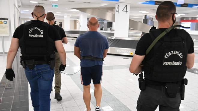 """Rendőrök kísérnek a Liszt Ferenc-repülőtéren 2021. június 24-én egy Teneriféről hazahozott 51 éves magyar férfit, akit azzal gyanúsítanak, hogy részt vett az úgynevezett """"kötözős"""" rablássorozatban. A gyanú szerint Sz. Tamás szervezte a 2015. március 13-i leányfalui fegyveres rablást, illetve a 2016. augusztus 8-án, Biatorbágyon elkövetett támadáskor rabolt értékek orgazdája volt. Ezen felül 2017-től rendszeresen kereskedett amfetaminnal. A bűncselekmények elkövetésére létrehozott bűnszervezet országszerte ténykedett 2010-től, a rablások mellett a kábítószer-kereskedelmet is folytattak, módszerük jellemzője volt, hogy a sértetteket megkötözték. MTI/Mihádák Zoltán"""