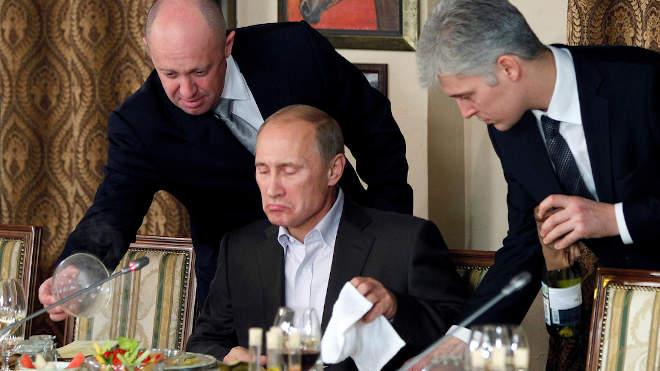 2011. november 11: Jevgenyij Prigozsin (balra) üzletember ételt szolgál Vlagyimir Putyinnak (középen) Prigozsin Moszkva melletti éttermében